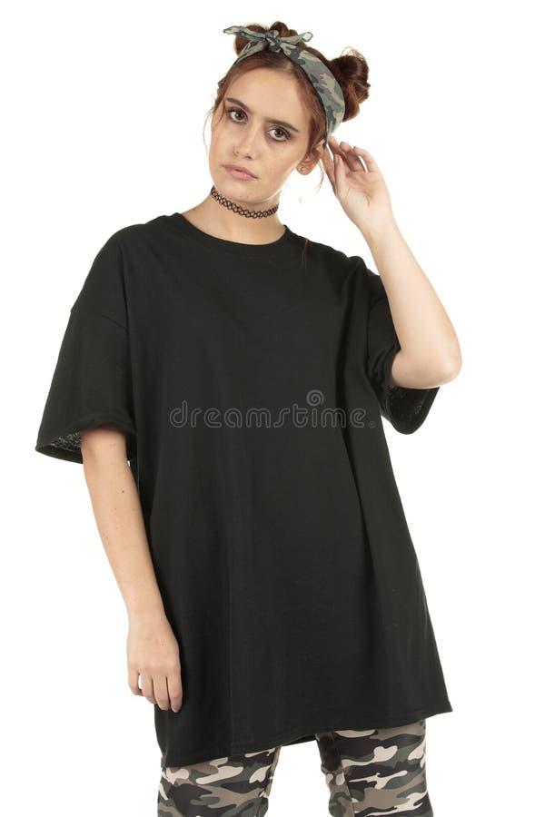 Modelo urbano del desgaste de la calle de la mujer en cargo del camo y una camiseta negra de gran tamaño con el copia-espacio foto de archivo libre de regalías