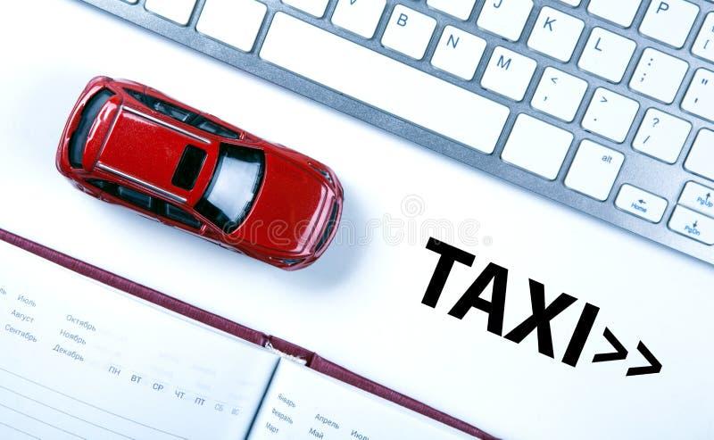 Modelo vermelho do carro perto do teclado no conceito de chamar um táxi fotografia de stock royalty free