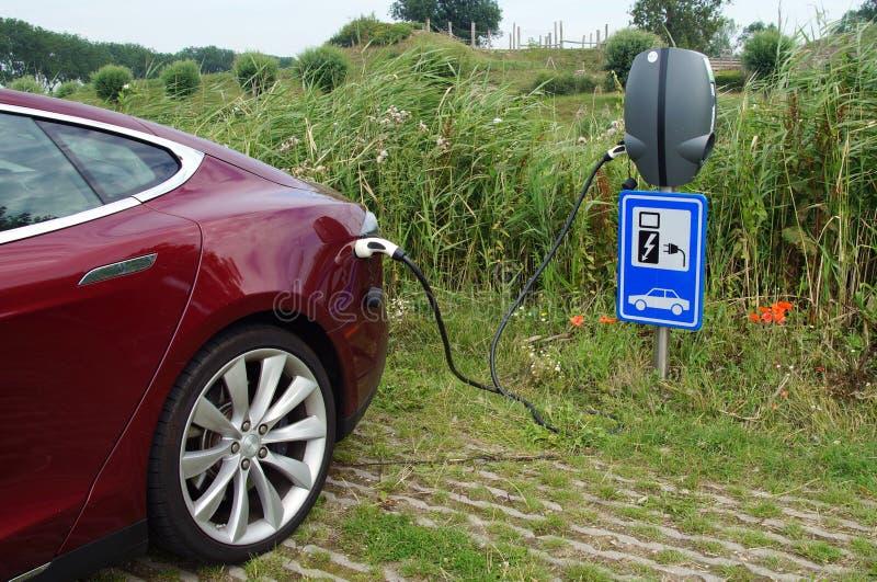 Modelo vermelho S de Tesla que está sendo carregado fotografia de stock