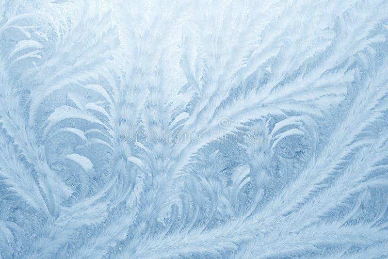 Modelos de Frost en el vidrio de la ventana en la estación del invierno Textura del vidrio helado Fondo para una tarjeta de la in imagen de archivo