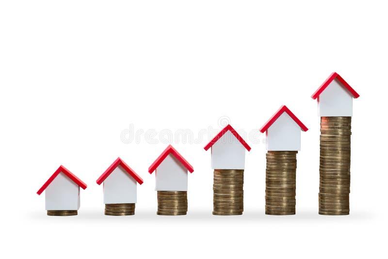 Modelos de la casa encima de aumentar monedas apiladas foto de archivo