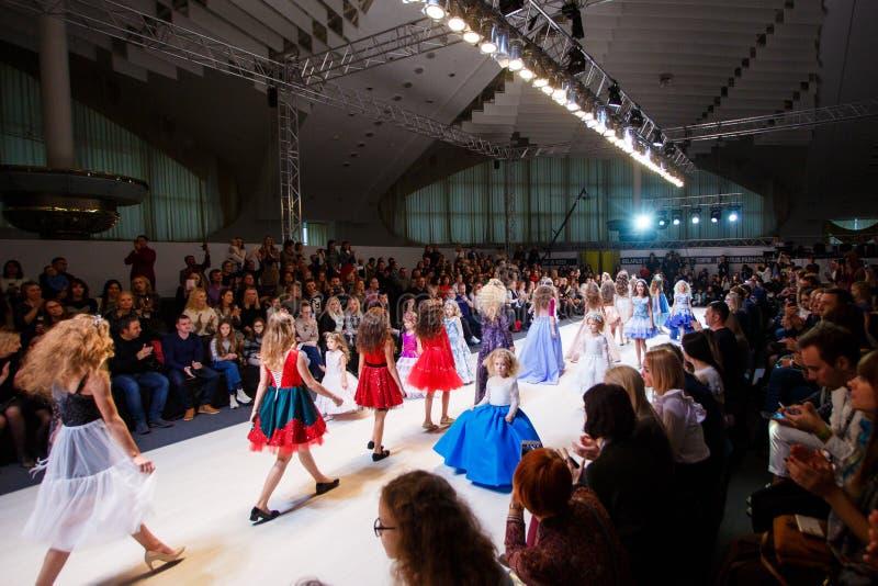 Modelos de los niños que van abajo de la prolongación del andén en la demostración de la semana de la moda fotos de archivo libres de regalías