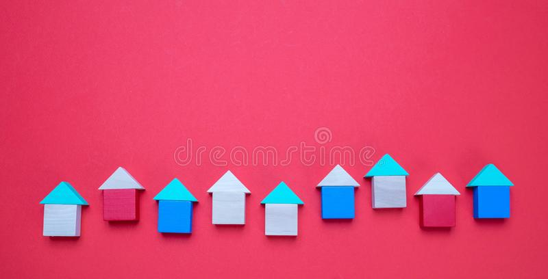Modelos de madeira pequenos da casa de blocos com os telhados no fundo vermelho imagem de stock royalty free