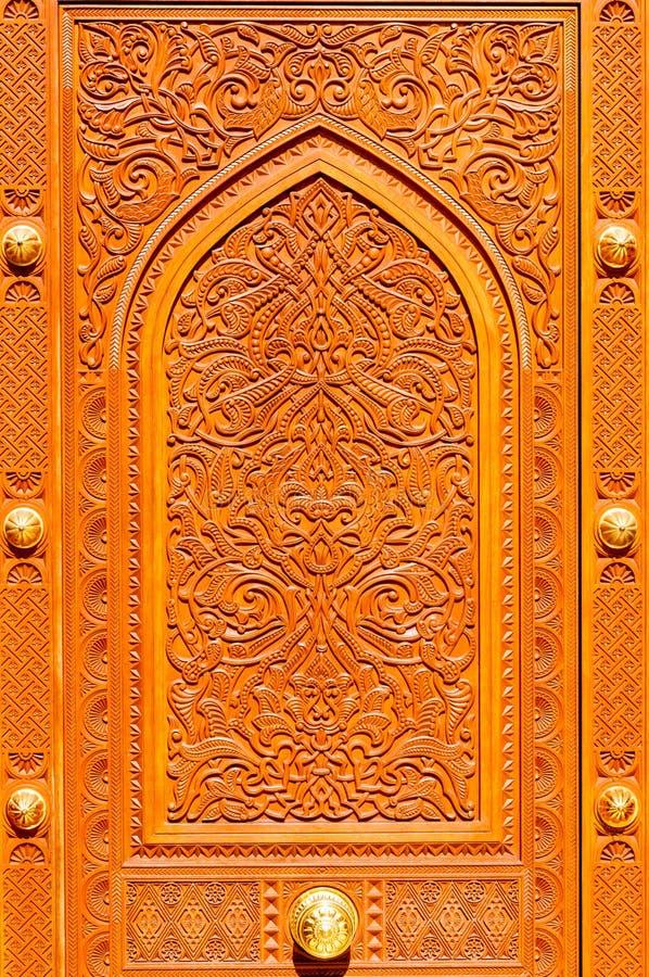 Modelos de Oriente Medio en una puerta de madera de la mezquita de Sultan Qaboos Grand, Muscat, Omán imagenes de archivo
