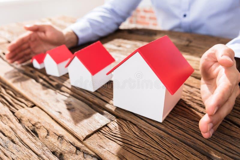 Modelos de Protecting The House do homem de negócios com mãos imagens de stock royalty free