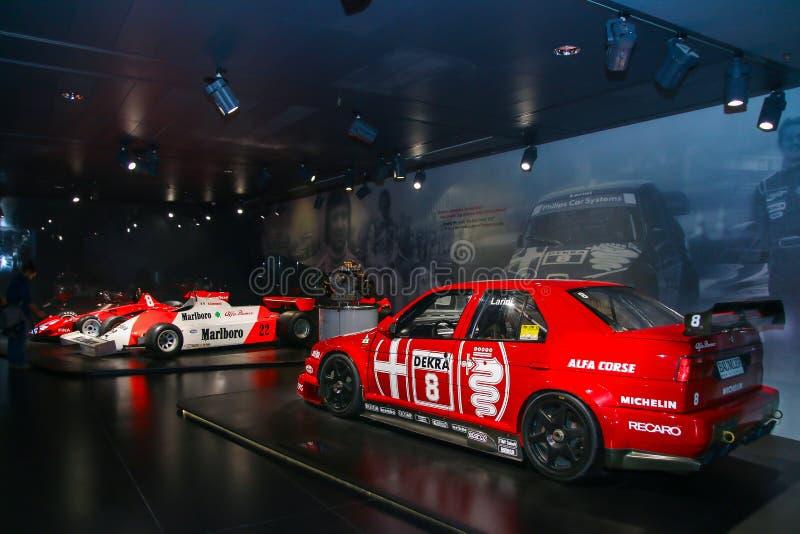 Modelos do si DTM e da fórmula 1 de Alfa Romeo 155 na exposição no museu histórico Alfa Romeo imagem de stock