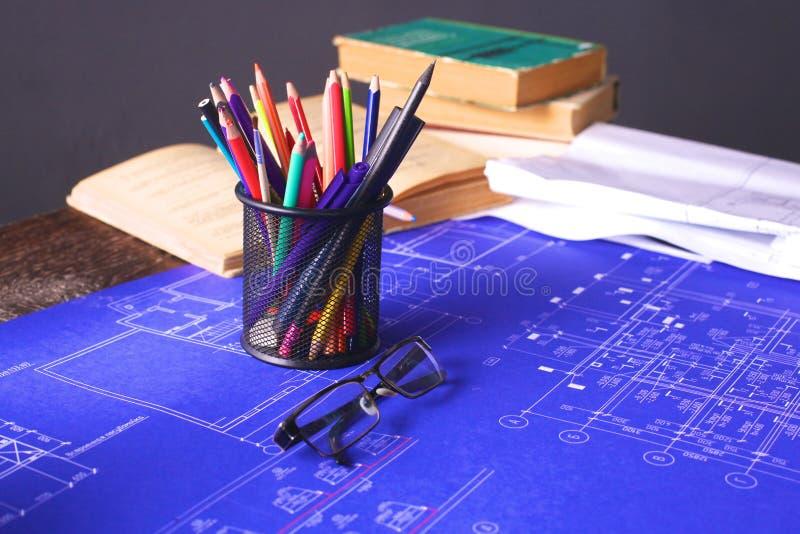 Modelos e rolos do modelo e instrumentos de desenho arquitetónicos no worktable imagem de stock