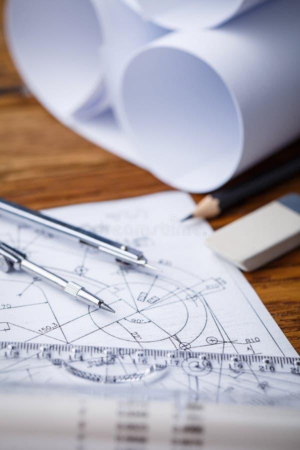 Modelos e rolos do modelo e instrumentos de desenho arquitetónicos no worktable imagens de stock royalty free