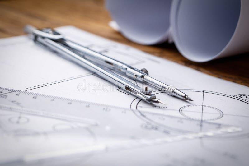 Modelos e rolos do modelo e instrumentos de desenho arquitetónicos no worktable Compasso de desenho, planos civil imagem de stock