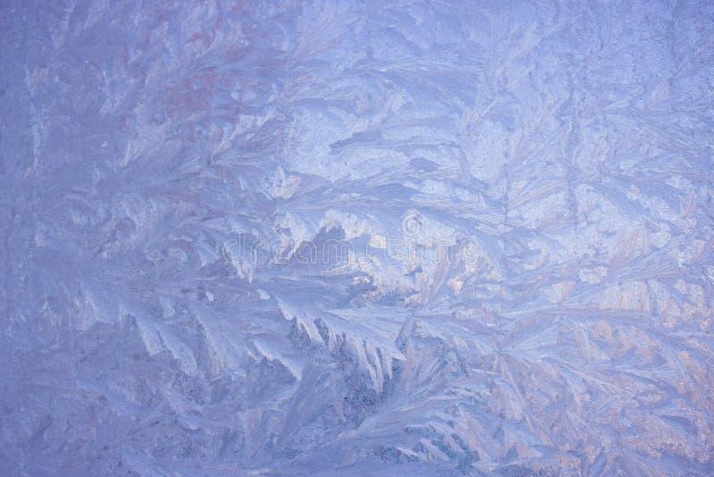 Modelos fríos de la helada sobre el vidrio imagen de archivo