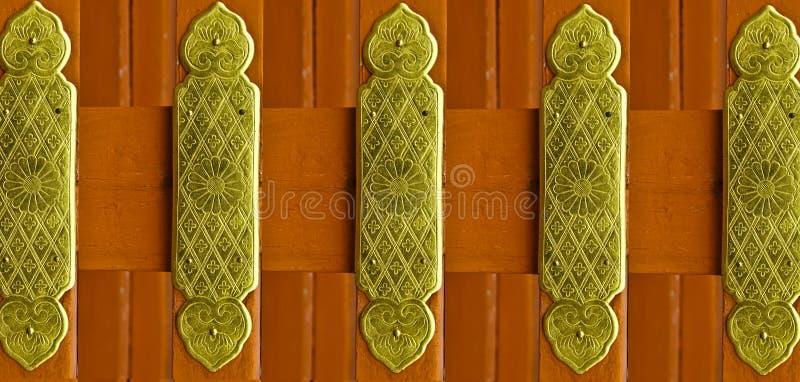 Modelos hermosos en un arreglo de la placa de cobre amarillo en la madera del color rojo imágenes de archivo libres de regalías