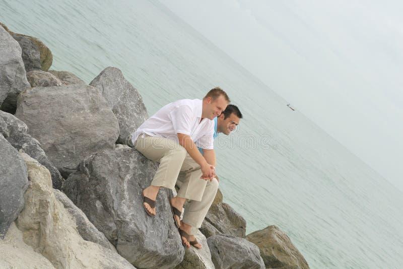 Modelos masculinos que sentam-se em rochas fotografia de stock royalty free