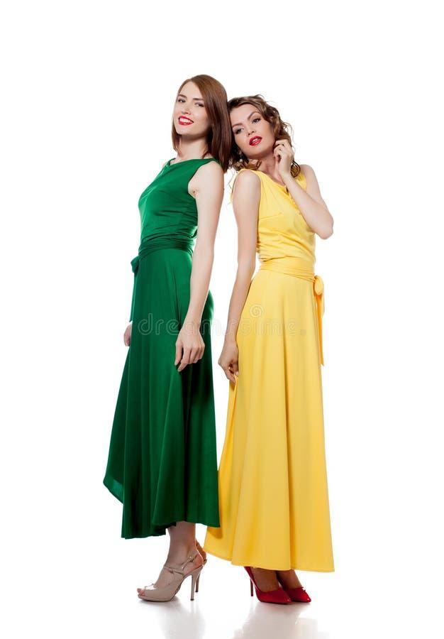 Modelos novos bonitos que levantam em vestidos coloridos fotografia de stock royalty free