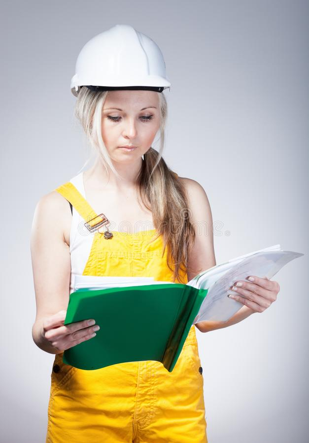 Modelos novos da leitura do trabalhador da construção da mulher do arquiteto foto de stock