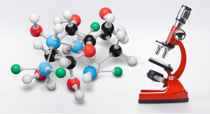 Modelos químicos da molécula com o microscópio no branco fotografia de stock