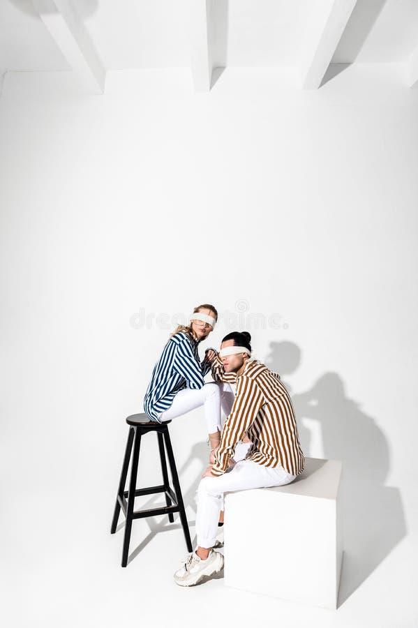 Modelos que levantam para a calças branca vestindo da promoção e camisa listrada fotos de stock royalty free