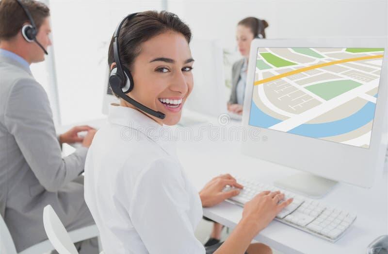 modelos que llevan el sistema de la cabeza que se sienta delante del ordenador contra fondo de la oficina imagen de archivo libre de regalías