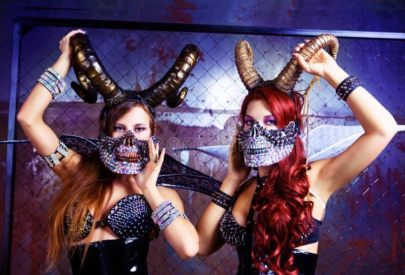 Modelos que llevan el traje de Halloween del cuero y de los cuernos imagen de archivo