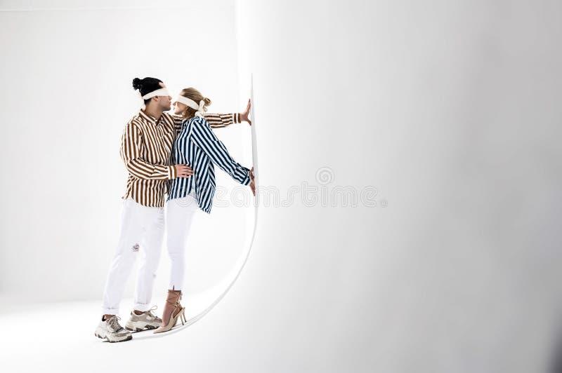 Modelos que vestem as calças brancas e as camisas listradas que levantam perto da parede branca imagem de stock