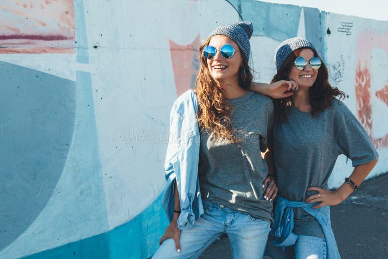 Modelos que vestem o tshirt liso e os óculos de sol que levantam sobre o wa da rua fotografia de stock