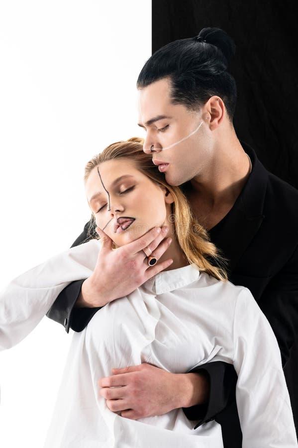 Modelos que vestem a roupa preto e branco e que têm linhas em suas caras foto de stock