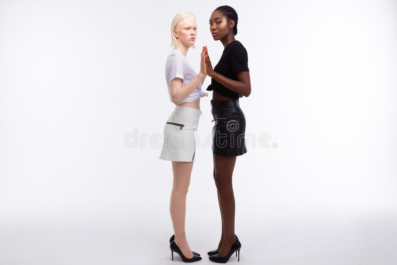 Modelos que vestem saias preto e branco e os t-shirt que levantam junto fotos de stock