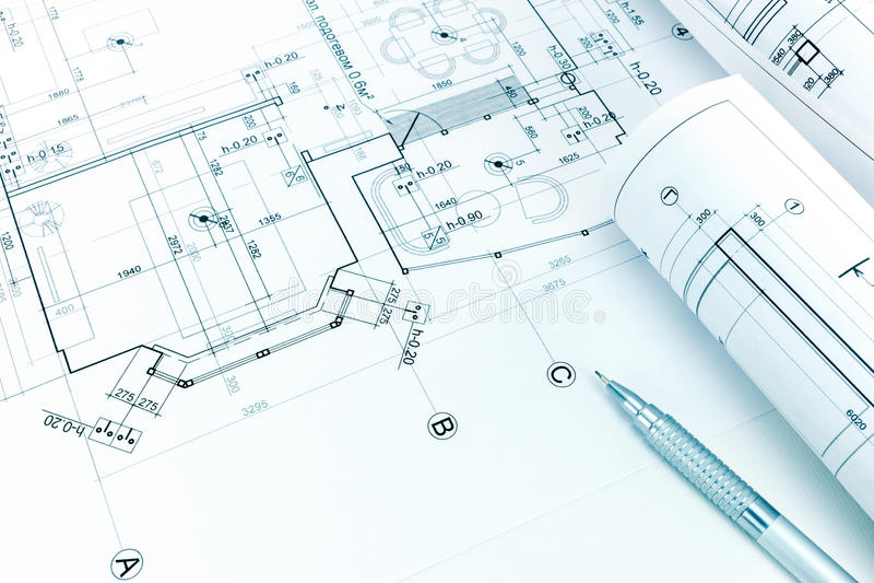 Modelos y lápiz arquitectónicos rodados en el dibujo del plan de piso foto de archivo libre de regalías