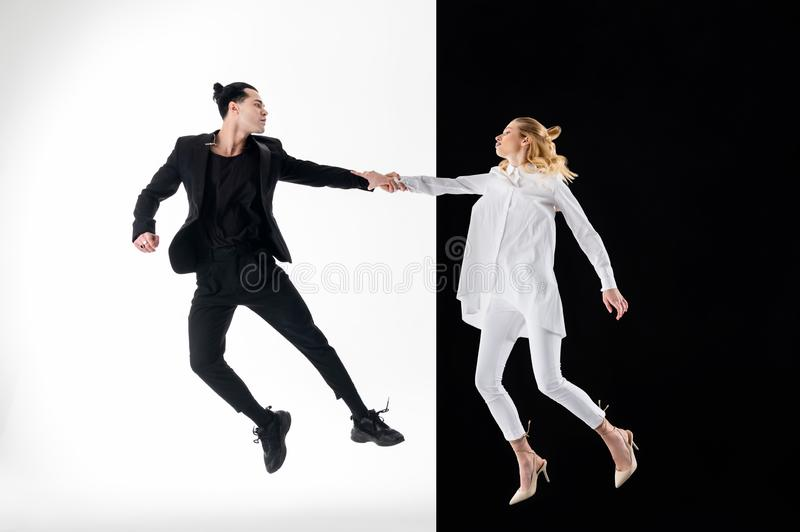 Models in black and white clothing jumping for nice shot royalty free stock image