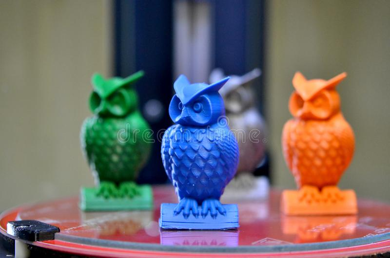 The models of owls created on the 3d printer stand on the desktop. Of 3d printer close-up. Progressive modern additive technologies 4.0 industrial revolution royalty free stock images