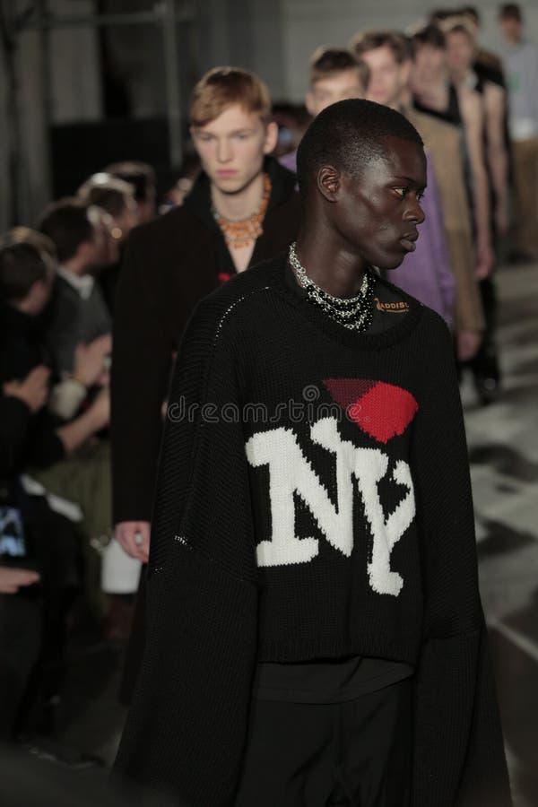 Models walk the runway finale at the Raf Simons fashion show. NEW YORK, NY - FEBRUARY 01: Models walk the runway finale at the Raf Simons fashion show during stock photography