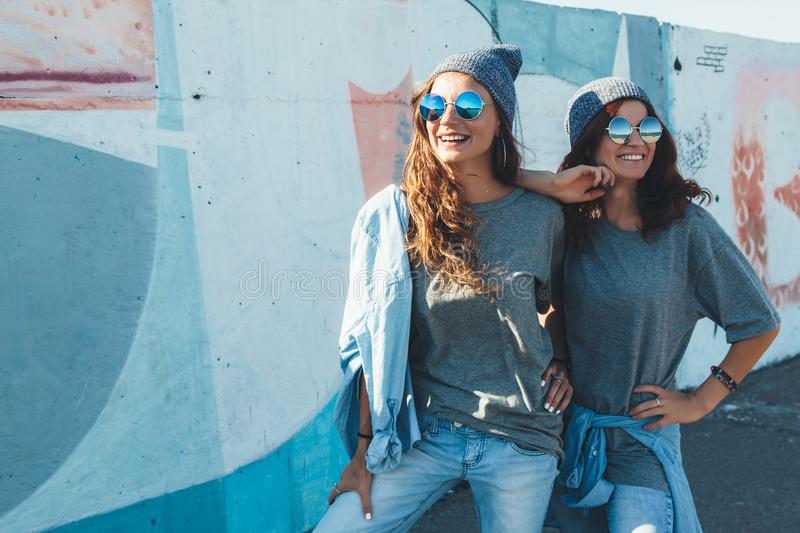 Models wearing plain tshirt and sunglasses posing over street wa stock photography