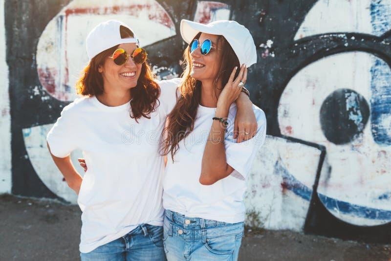 Models wearing plain tshirt and sunglasses posing over street wa royalty free stock image