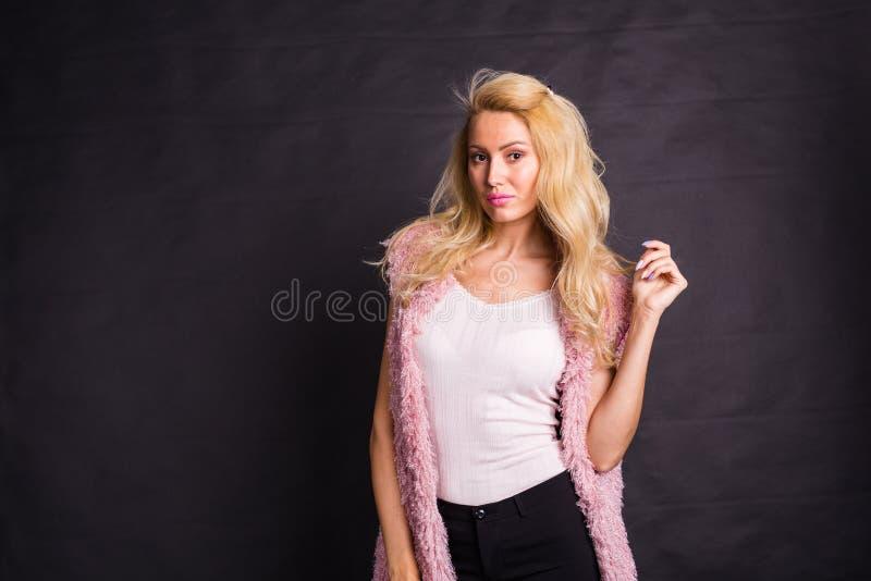 Modelujący, moda, ludzie pojęcie młodej poważnej blondynki w menchia żakiecie nad czarnym tłem z kopii przestrzenią obraz stock
