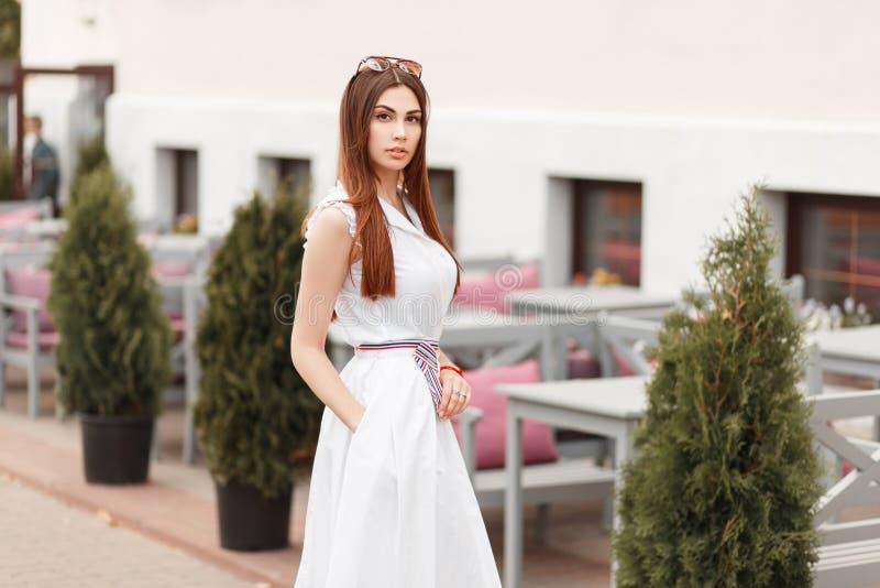 Modelvrouw in het modieuze witte kleding stellen in de stad royalty-vrije stock afbeelding