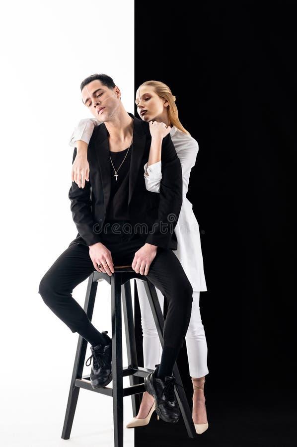 Modelzitting op stoel en aantrekkelijke vrouw die zich achter hem bevinden stock foto