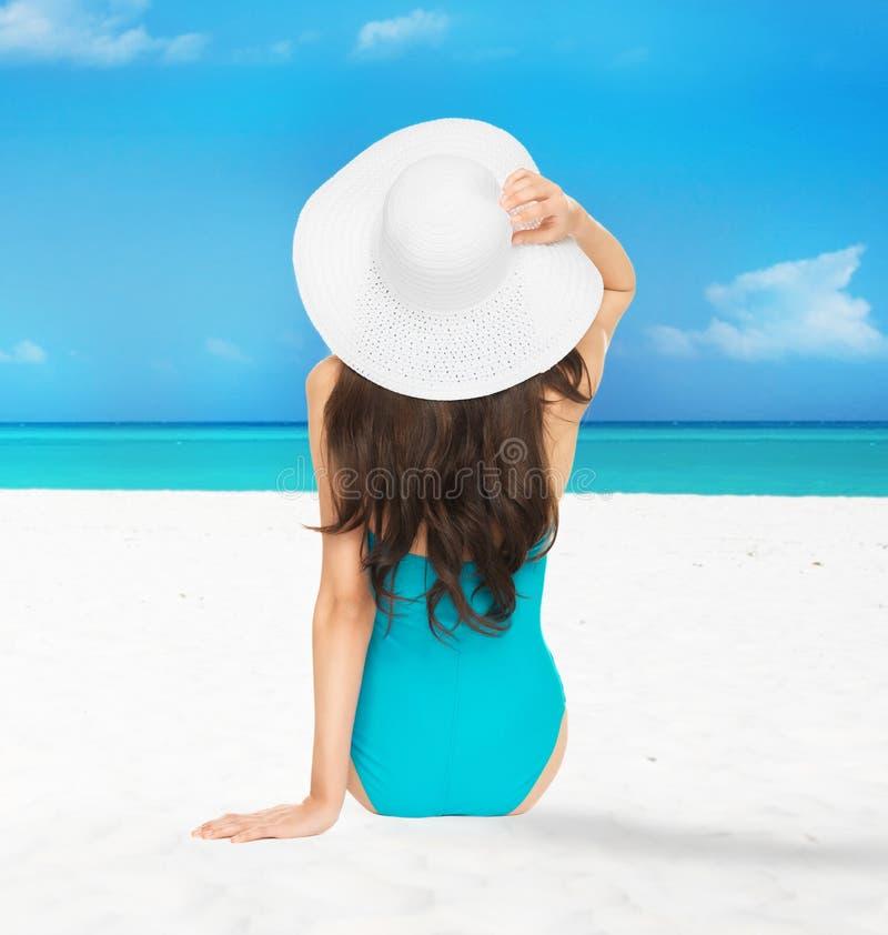 Modelzitting in zwempak met hoed royalty-vrije stock afbeelding