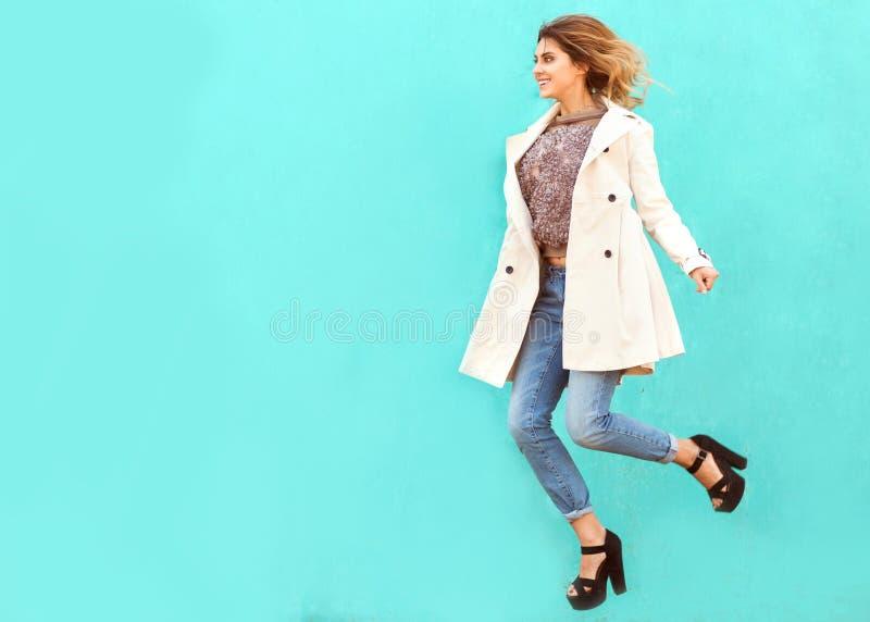 Modemädchen in den runden Gläsern steht, springend nahe einem Türkis wa lizenzfreie stockfotografie