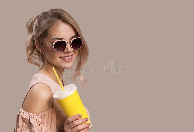 Modemädchen in einem großen Hut und in der Sonnenbrille auf einem farbigen Hintergrund lizenzfreie stockfotografie