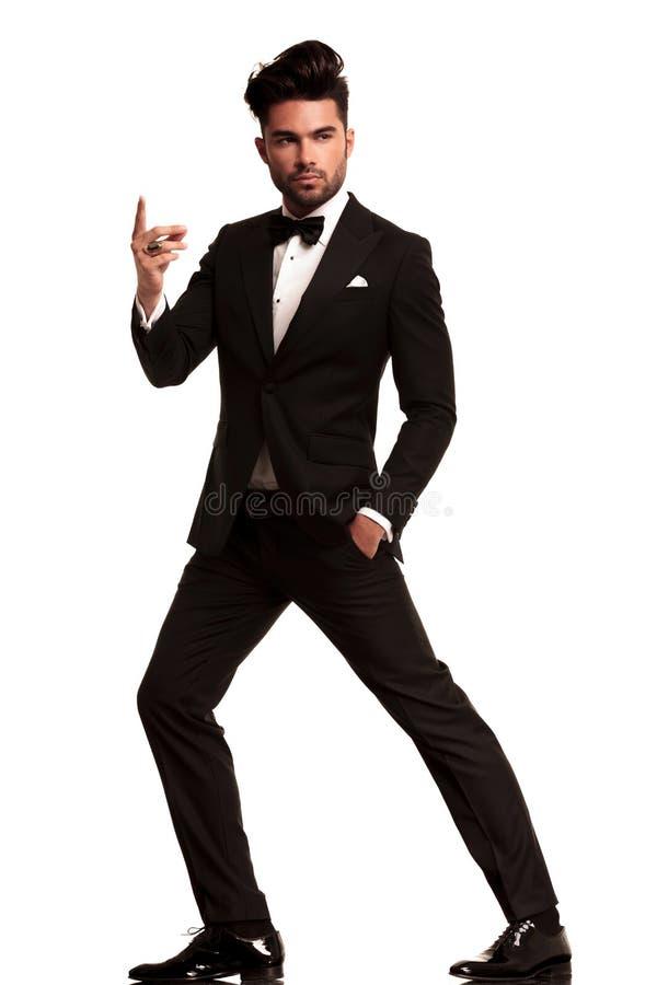 Modemann im Smoking, das seinen Finger reißt lizenzfreie stockfotos