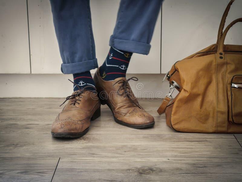 Modemannen lägger benen på ryggen i indigoblå marinblåa flåsanden, marinankarsockor, läderskor och lädertotopåse arkivfoto