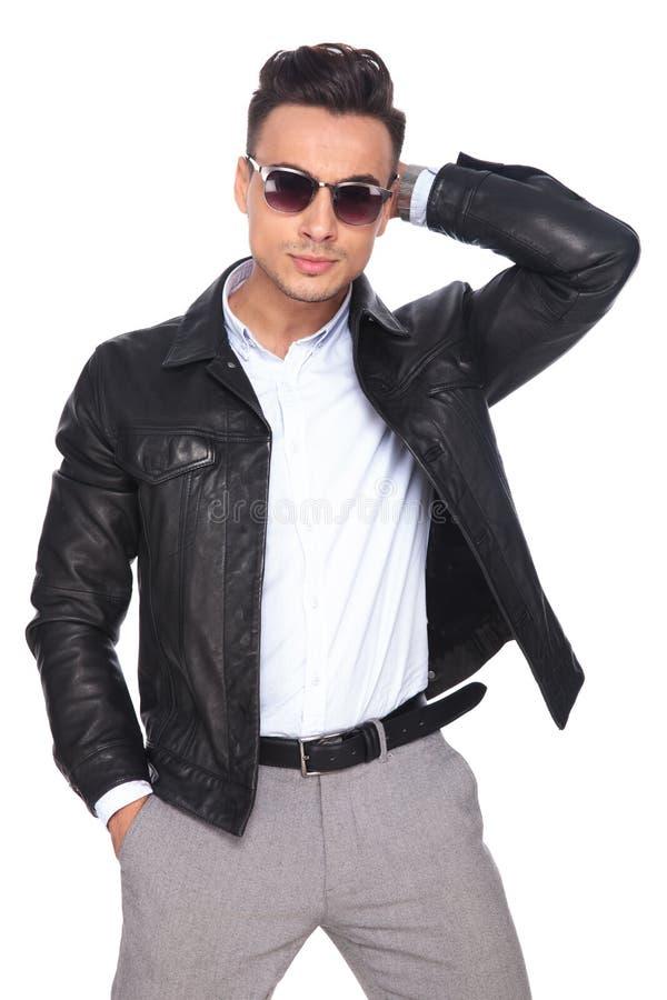 Modemannen som bär solglasögon, ordnar hår, medan stå royaltyfria foton