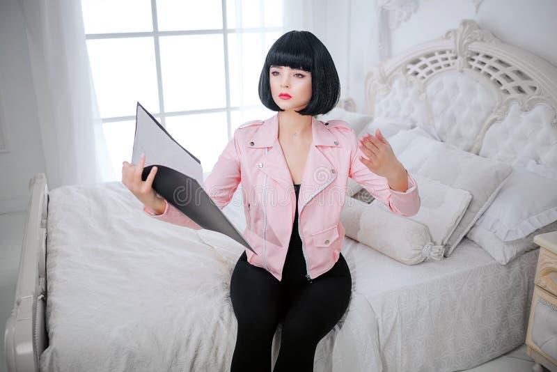 Modemissfoster Fejkar den syntetiska flickan för glamour, dockan med tom blick, och kort svart hår rymmer mappen, medan sitta på royaltyfri fotografi