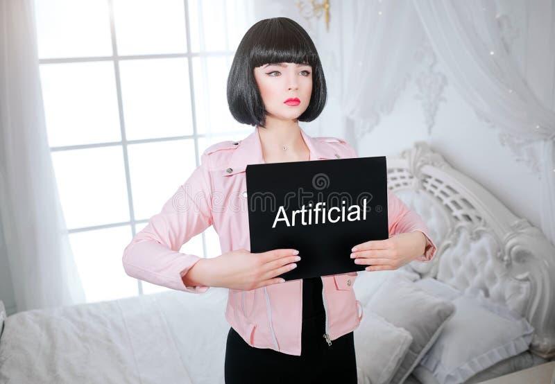 Modemissfoster Glamourflickan, fejkar dockan med tom blick, och kort svart hår rymmer papper med konstgjord stund för ord royaltyfria foton