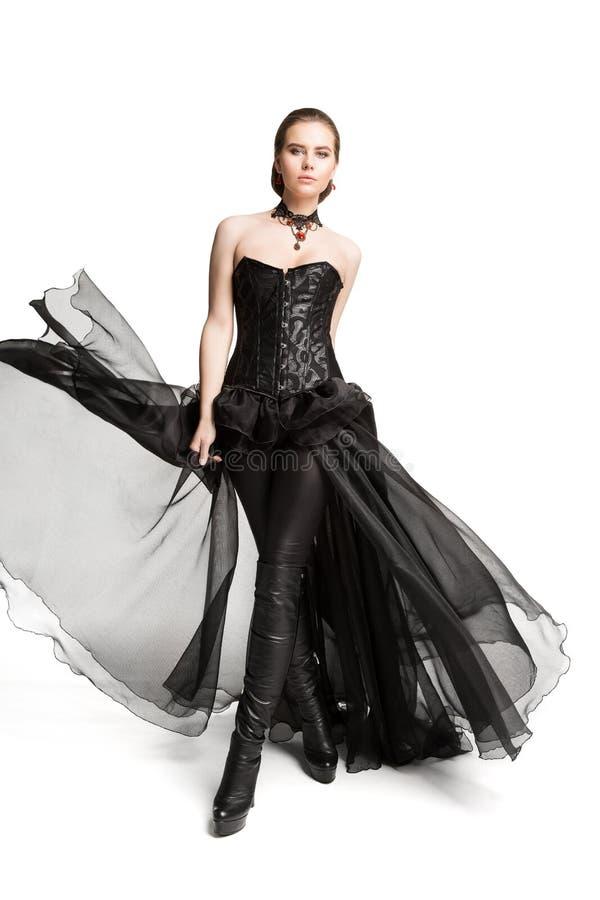 Modemodell Black Corset Dress, läderflåsanden, härlig kvinna i den gotiska kappan, vit arkivbild