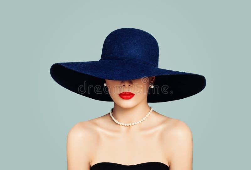 Modemodell för elegant kvinna med röd kantmakeup som bär den klassiska hatten och vita pärlor, stående fotografering för bildbyråer