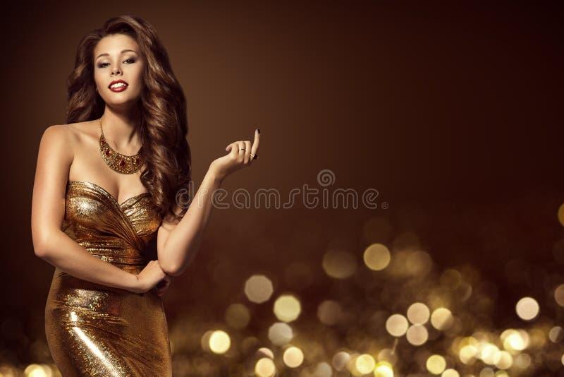 Modemodell Gold Dress, elegant ung kvinna i guld- kappa royaltyfria bilder