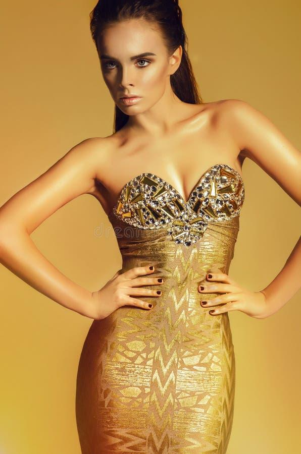 Modemodell i guld- klänning fotografering för bildbyråer