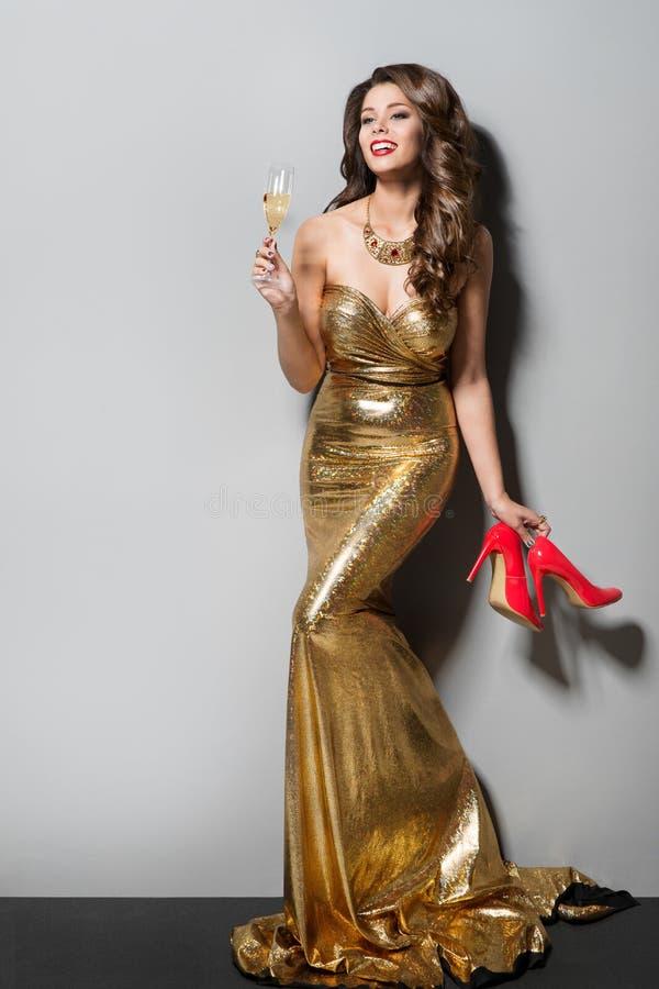 Modemodell, i lång guld- dans och att dricka för klänning, lycklig elegant kvinna, skor för hög häl royaltyfri fotografi