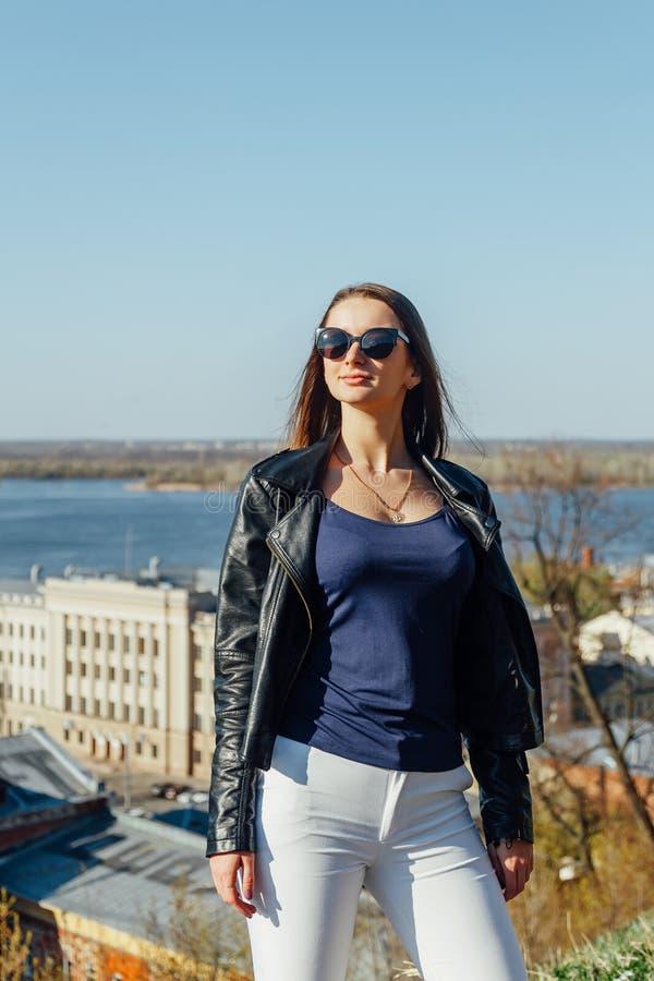 Modemodell i solglasögon och posera för svartläderomslag som är utomhus- royaltyfri fotografi