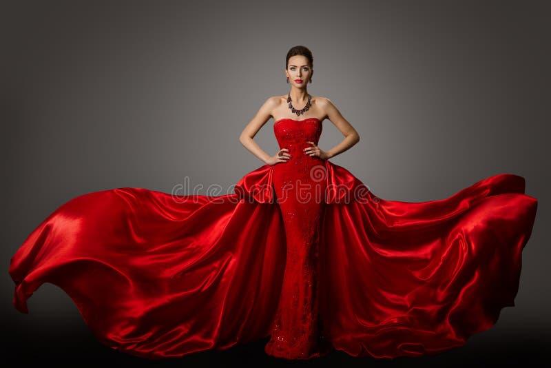 Modemodell Red Dress, kvinna i långt den vinkande kappan för fladdra, skönhetstående arkivbild
